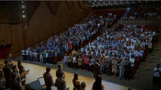 Fig. 1: Captura de tela do vídeo em que o cantor Tatau, junto com o NEOJIBA, canta o Hino ao Dois de Julho. A gravação foi feita em 2010, no Teatro Castro Alves, em Salvador-BA. Clique na imagem para assistir ao vídeo.